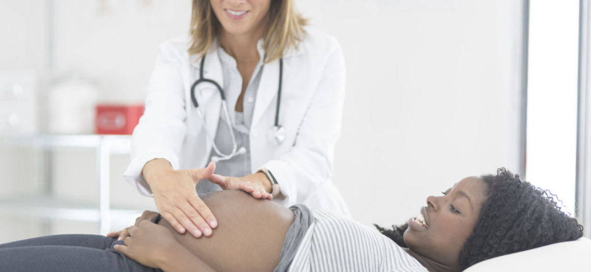Pregnant woman at a checkup with her female doctor